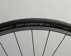 Continental Grand Prix Force II road bike tire on a rolling resistance test machine
