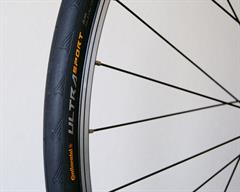 Continental Ultra Sport II road bike tire on a rolling resistance test machine
