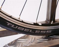 Close up of a Schwalbe One Tubeless tire on a rolling resistance test machine